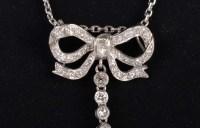 Pendentif en or gris stylisée d'un noeud de ruban serti de diamants 1900