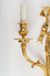 A pair of wall lights in the Louis XVI style.