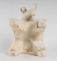 Statue en albâtre représentant une petite fille assise sur un tabouret et jouant avec des chaussures .