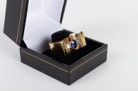 Bague chevalière en or jaune 18 kt et platine, ornée d'un saphir ovale epaulé de diamants