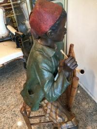 Enfant noir en terre cuite sur une chaise en bambou et cannage. Réf: 356